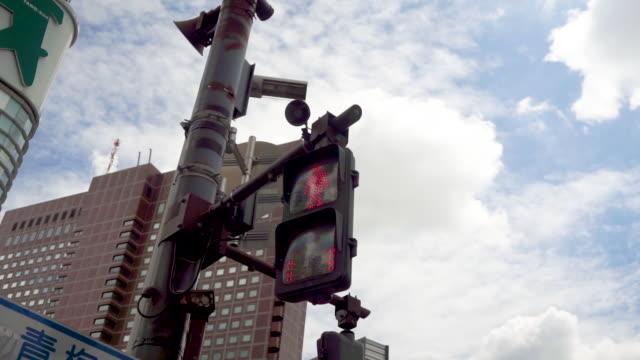 semaforo hd overhead che cambia con il cielo blu in città - segnale per macchine e pedoni video stock e b–roll