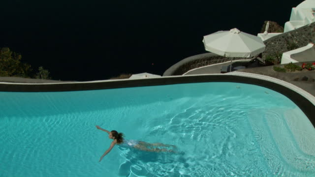 overhead view of a woman swimming - infinity pool stock videos & royalty-free footage