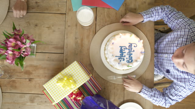 overhead view of boy at dining table with birthday cake. - birthday cake stock videos & royalty-free footage