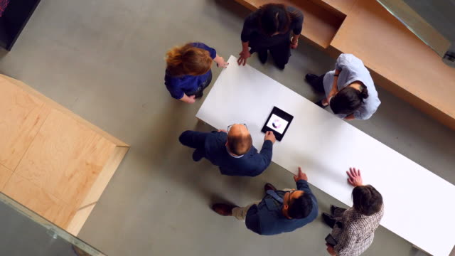vídeos de stock e filmes b-roll de ms pan overhead view of business colleagues discussing project on digital tablet - ideas