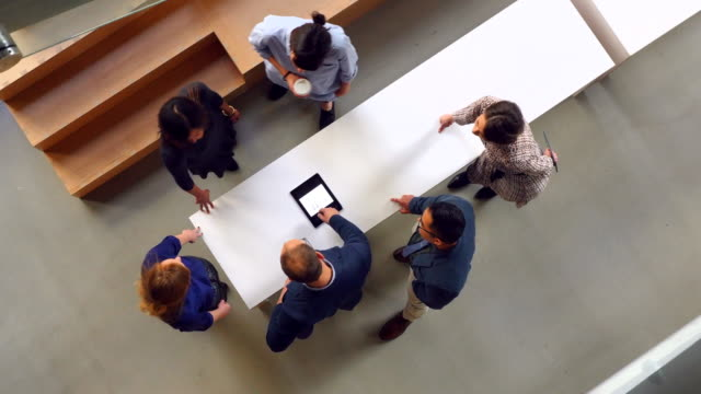 MS PAN Overhead view of businessman leading project discussion on digital tablet