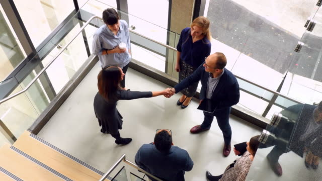 MS TS Overhead view of businesspeople shaking hands on office stairs