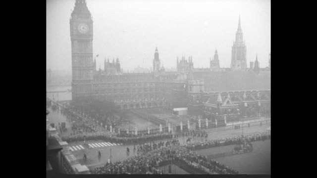 stockvideo's en b-roll-footage met overhead view of central london where throngs of mourners watch the passing of king george vi's casket on a gun carriage drawn by horses and escorted... - hoed