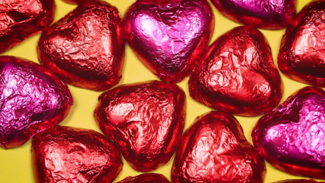overhead view of chocolate love hearts wrapped in shiny foil rotating - large group of objects stock videos & royalty-free footage