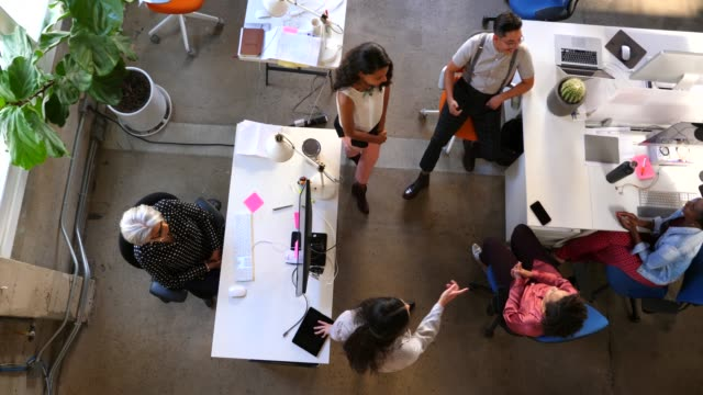 pan overhead view of colleagues having project meeting in design studio - cooperation stock videos & royalty-free footage