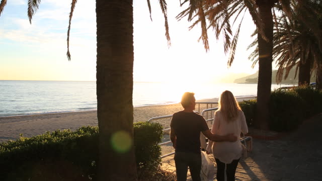 Overhead view of couple watching sunset over beach, promenade