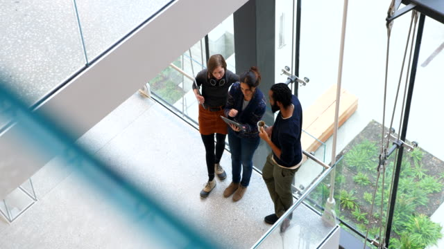 ms overhead view of coworkers discussing project on digital tablet on stairs of office building - university of washington stock videos & royalty-free footage