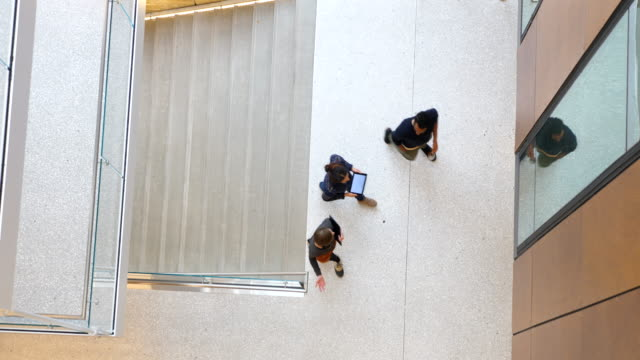 vídeos de stock e filmes b-roll de ms overhead view of coworkers in discussion while walking up office stairs - três pessoas