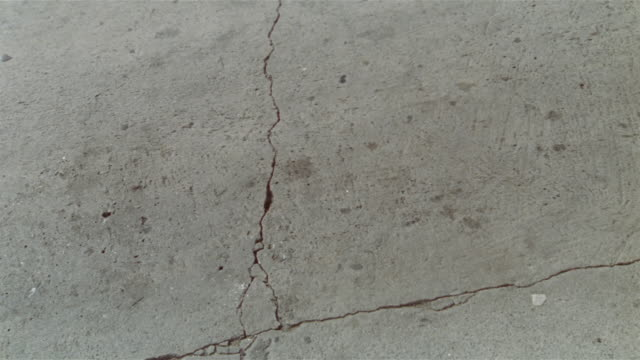 Overhead view of crack in pavement / woman driving past in silver convertible / Los Angeles, California