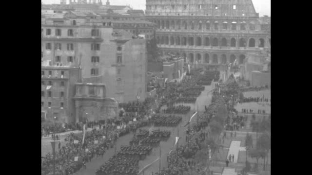 Overhead view of crowd in Piazza Venezia in front of Victor Emmanuel Monument Fascist Black Shirts marching by on street in front of them / crowd...