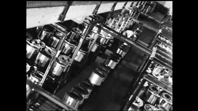 vidéos et rushes de overhead view of factory full of metal reels spinning; worker on cart rolls by with metal disks and another man checks on them - 1940 1949