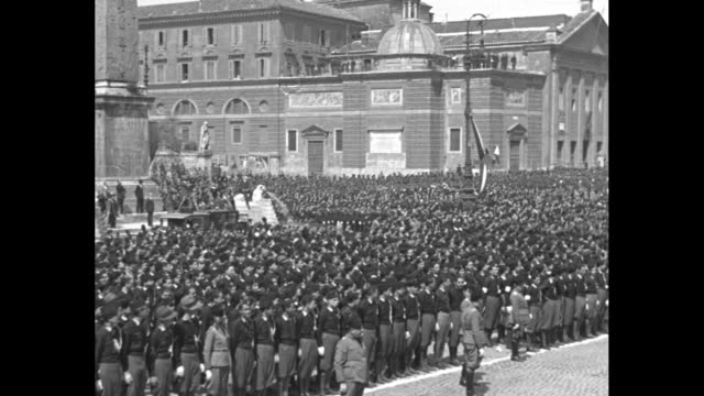 overhead view of fascist black shirts gathered in formations in square many waving / cu il duce benito mussolini / pan across huge crowd of black... - parade stock videos & royalty-free footage