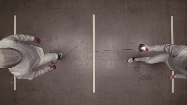 overhead view of fencer avoiding opponent's epee and strikes back
