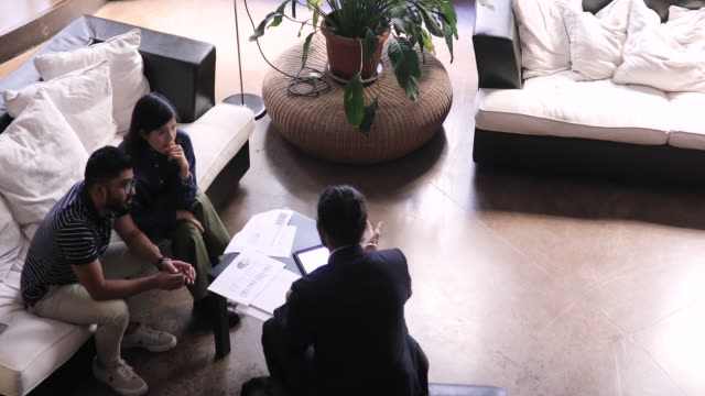 overhead view of financial advisor explaining investment graphs to couple at home - politics and government stock videos & royalty-free footage