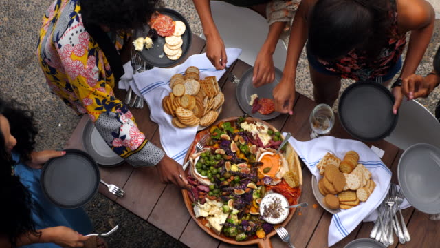 pan overhead view of friends enjoying appetizers during pool party - food stock videos & royalty-free footage