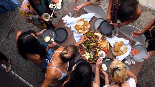 pan overhead view of friends enjoying appetizers during pool party - abundance stock videos & royalty-free footage