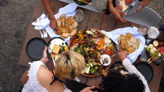 pan overhead view of friends serving plates of appetizers during pool party - appetizer stock videos & royalty-free footage