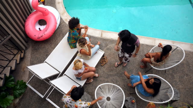 ms overhead view of friends sitting by hotel pool during party - 20 29 years stock videos & royalty-free footage