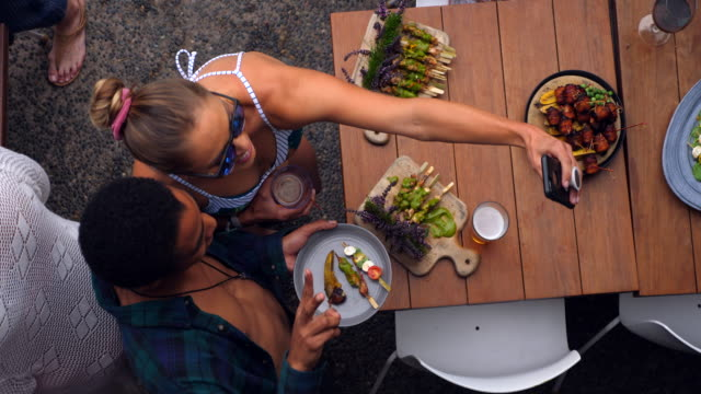 ms overhead view of friends taking selfie while eating appetizers during pool party - sunglasses stock videos & royalty-free footage