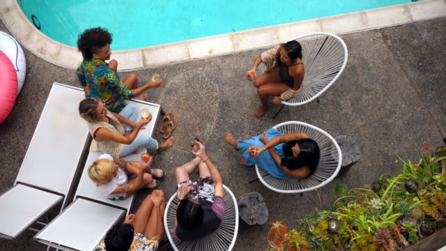 pan overhead view of friends toasting drinks by hotel pool during party - bassängkant bildbanksvideor och videomaterial från bakom kulisserna
