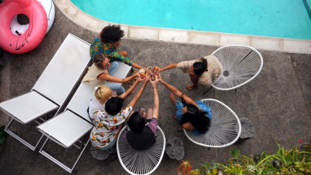 ms overhead view of friends toasting drinks by hotel pool during party - cocktail stock videos & royalty-free footage