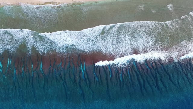 Overhead view of gentle waves breaking on Pacific Atoll
