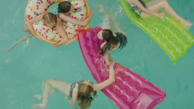 overhead view of girls swimming and playing in swimming pool / cedar hills, utah, united states - inflatable stock videos and b-roll footage