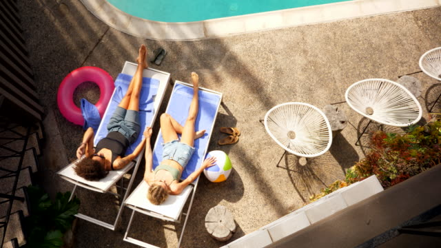 stockvideo's en b-roll-footage met ms overhead view of lesbian couple holding hands while relaxing in lounge chairs by hotel pool - leunen