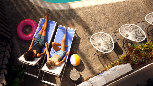 ms overhead view of lesbian couple holding hands while relaxing in lounge chairs by hotel pool - lounge chair stock videos & royalty-free footage