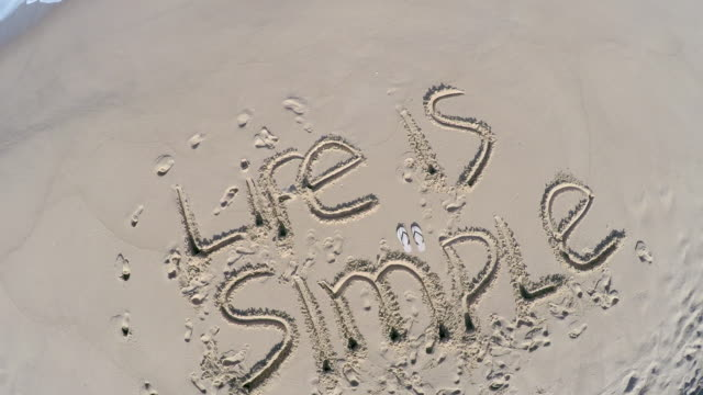 Overhead view of 'Life is Simple' written on beach