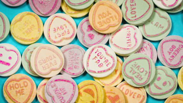 overhead view of love heart sweets slowly revolving - confectionery stock videos & royalty-free footage