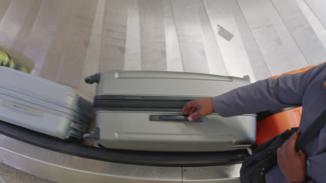 overhead view of luggage as african-american businessman grabs bag off conveyor belt in baggage claim. - fließband stock-videos und b-roll-filmmaterial
