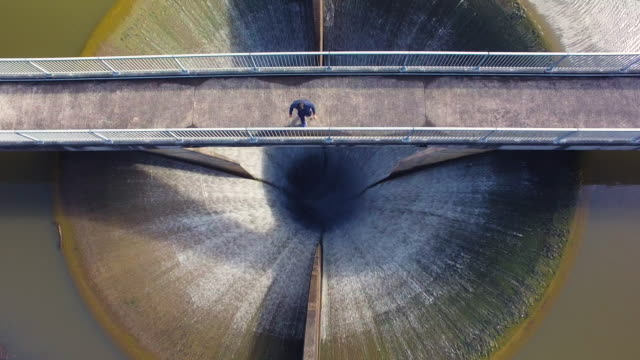 Overhead View Of Man Standing On Bridge And Looking At Water Going In Lower Huia Dam, Auckland, New Zealand.