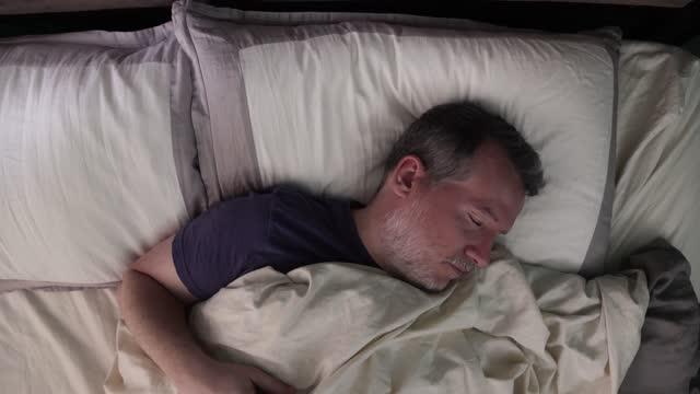 overhead-ansicht des reifen mannes zu stürzen und drehen im bett nicht schlafen - schlafenszeit stock-videos und b-roll-filmmaterial