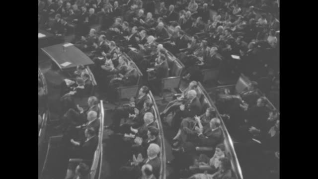 overhead view of members of us house of representatives sitting and applauding in house chamber / speaker of the house sam rayburn escorts newly... - speaker of the house stock videos and b-roll footage