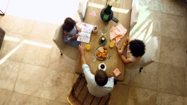 ms overhead view of smiling pregnant wife and husband sharing breakfast with daughter at dining room table - real wife sharing stock-videos und b-roll-filmmaterial