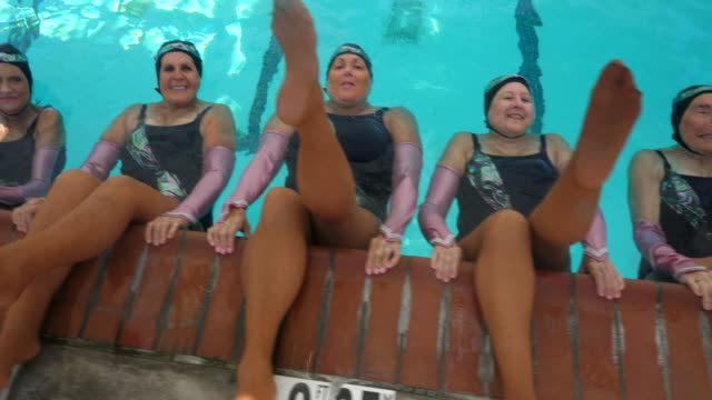 ms overhead view of smiling senior female synchronized swim team with legs up on edge of pool - wassersport stock-videos und b-roll-filmmaterial