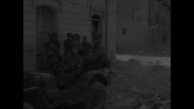 Overhead view of soldiers and equipment in city of Gela next to beach / view of city of Gela / soldiers marching down street in city / tank driving...