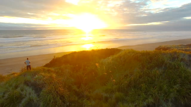 overhead view of sunset at muriwai beach, auckland, new zealand. - north island new zealand stock videos & royalty-free footage