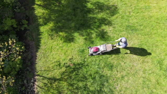 zo overhead view of teenage boy mowing grass in backyard on summer afternoon - one teenage boy only stock videos & royalty-free footage