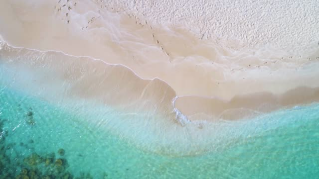 overhead view of waves and sand over a caribbean cay with turquoise waters - bahamas stock videos & royalty-free footage