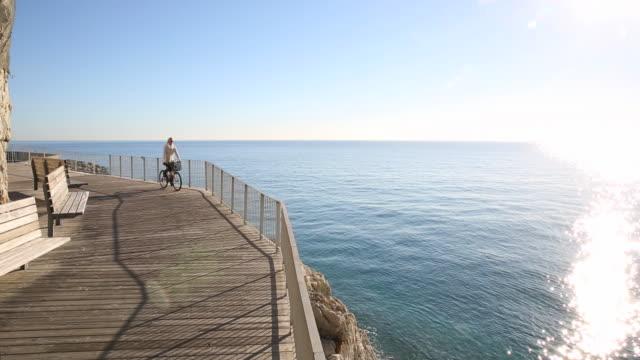 overhead view of woman biking along boardwalk, sea - solo una donna di età media video stock e b–roll