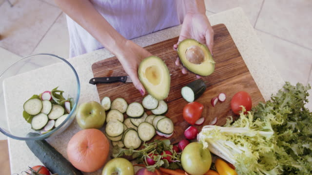 stockvideo's en b-roll-footage met overhead view of woman making a salad - gezonde voeding