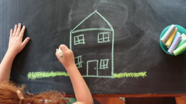vidéos et rushes de overhead view, young girl drawing a house and family with chalk on a table - dessin