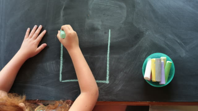 vidéos et rushes de overhead view, young girl drawing a house with chalk on a table - dessin enfant