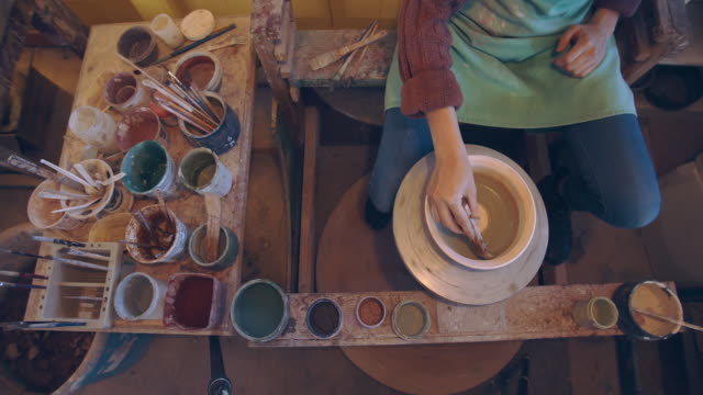 overhead view, cu young woman's hands painting a bowl in a ceramics studio - pottery stock videos & royalty-free footage