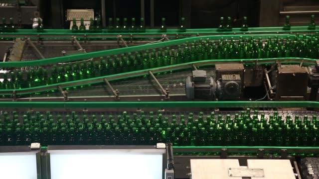 stockvideo's en b-roll-footage met overhead wide pan l r of bottles moving along multiple conveyors medium overhead views of bottles moving along conveyors pull focus medium wide side... - middelenmisbruik