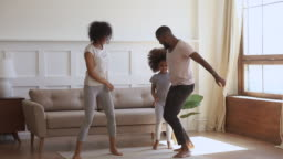 Overjoyed smiling african ethnicity family couple dancing with cute daughter.