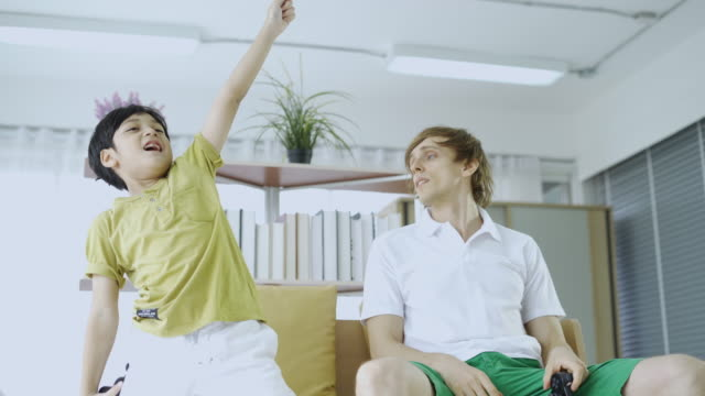 vídeos y material grabado en eventos de stock de overjoed joven adulto papá y lindo niño hijo jugadores jugando el videojuego - son