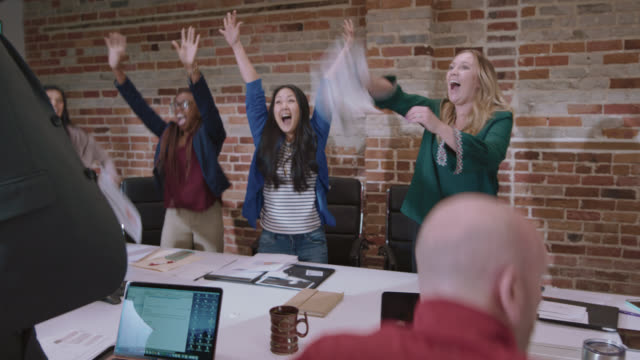 overjoyed young businesswomen cheer and high five as they celebrate in an office conference room - feiern stock-videos und b-roll-filmmaterial